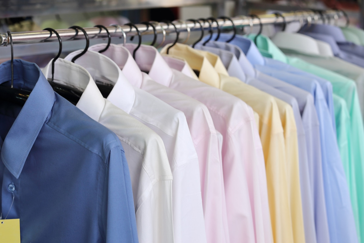 Men's plaid shirts in different colors on hangers in a retail shop